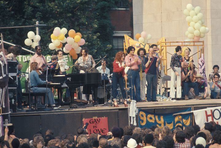 Barry Manilow (seated at piano) and Bette Midler (at center, in red) at a Gay Liberation rally at Washington Square Park on J