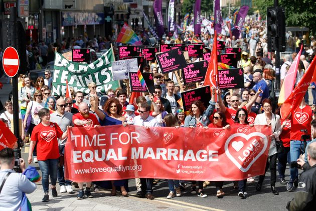 Activists campaigning for an end to Northern Ireland's ban on same-sex marriage take part in a parade...