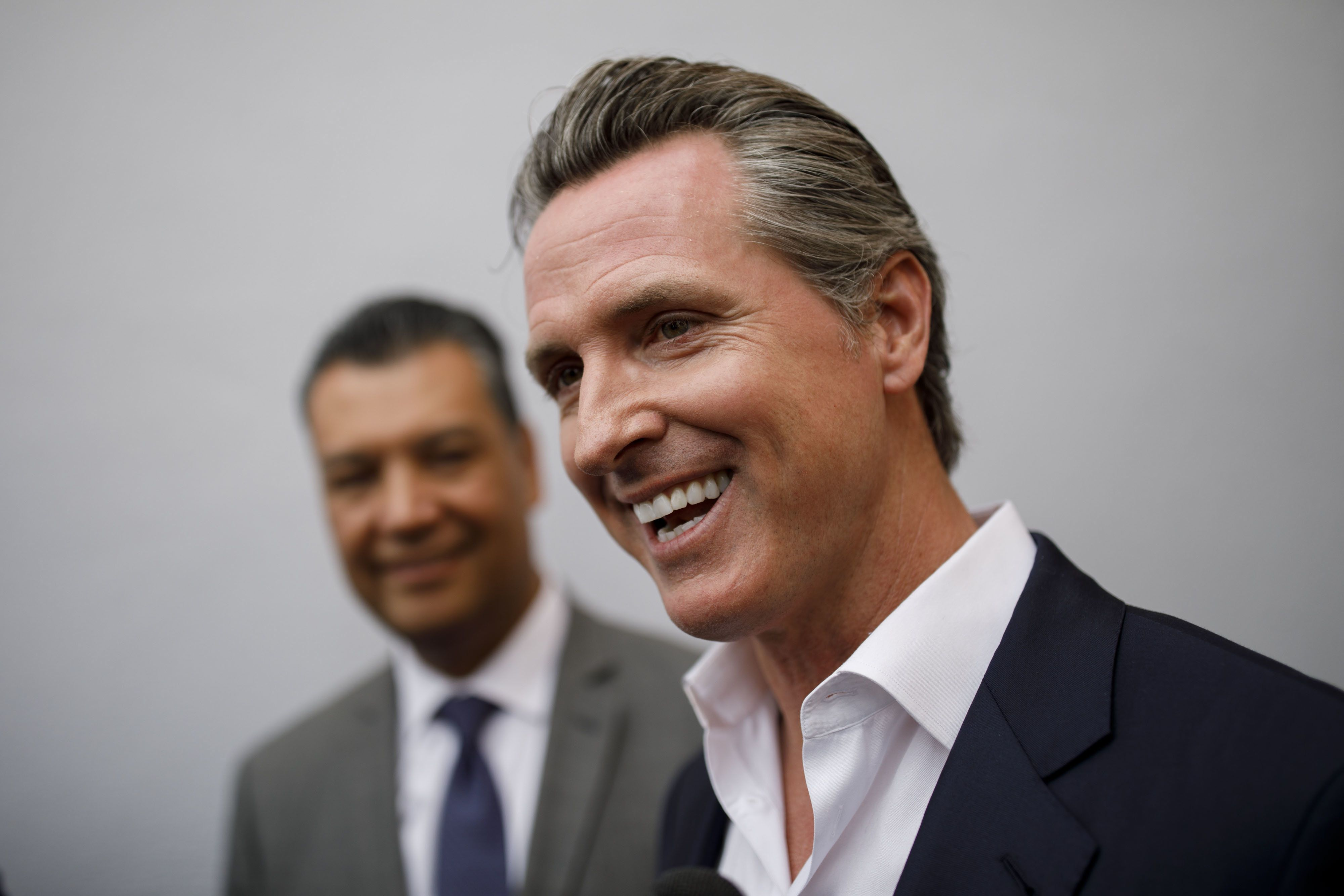 Gavin Newsom, Democratic candidate for governor of California, right, smiles while speaking with members of the media alongside Alex Padilla, California secretary of state, after a rally in Burbank, California, U.S., on Wednesday, May 30, 2018. The Democratic candidates running to replace Governor Jerry Brown -- Lieutenant Governor Newsom, former Los Mayor Antonio Villaraigosa and State Treasurer John Chiang-- have pledged to protect the rights of undocumented immigrants. Photographer: Patrick T. Fallon/Bloomberg via Getty Images