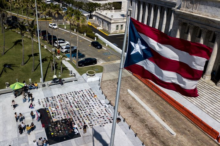 A Puerto Rican flag flies above empty pairs of shoes outside the island's Capitol building.
