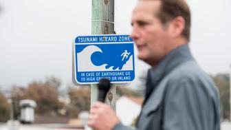 UNITED STATES - MAY 20: A tsunami hazard zone sign stands in the background as Harley Rouda, Democrat running for California's 48th Congressional district seat in Congress, speaks during his campaign rally in Laguna Beach, Calif., on Sunday, May 20, 2018. California is holding its primary election on June 5, 2018. (Photo By Bill Clark/CQ Roll Call)