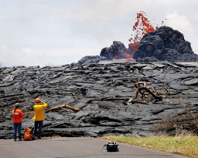 Officials from the U.S. Geological Survey Hawaiian Volcano Observatorywatch lava erupting from...