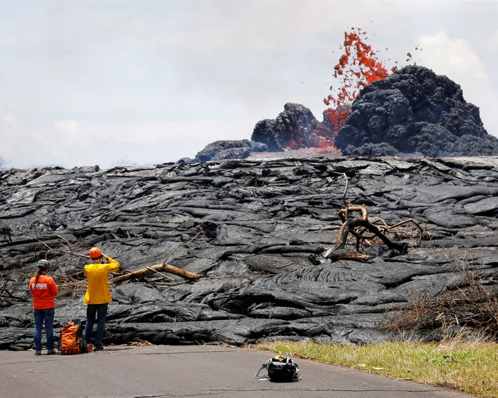 Officials from the U.S. Geological Survey Hawaiian Volcano Observatory watch lava erupting from a fissure in the Leilani