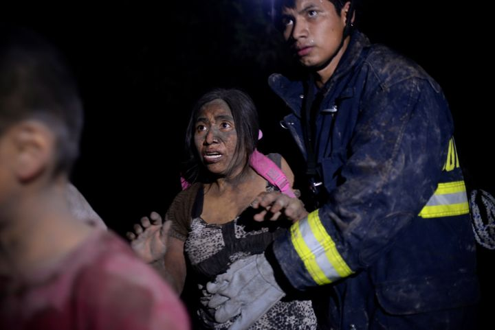 A rescue worker helps a woman covered with ash after Fuego volcano erupted violently in El Rodeo, Guatemala June 3, 2018.