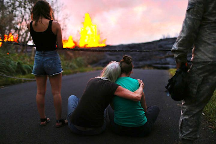 PAHOA, HI - MAY 23:  A resident (C) hugs her daughter as they watch lava erupting from a Kilauea volcano fissure in Leilani Estates, on Hawaii's Big Island, on May 23, 2018 in Pahoa, Hawaii. Officials are concerned that 'laze', a dangerous product produced when hot lava hits cool ocean water, will affect residents. Laze, a word combination of lava and haze, contains hydrochloric acid steam along with volcanic glass particles.  (Photo by Mario Tama/Getty Images)