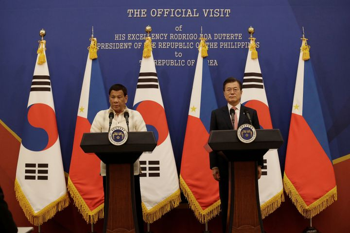 Duterte (L) with South Korean President Moon Jae-in a day after kissing a woman on stage.