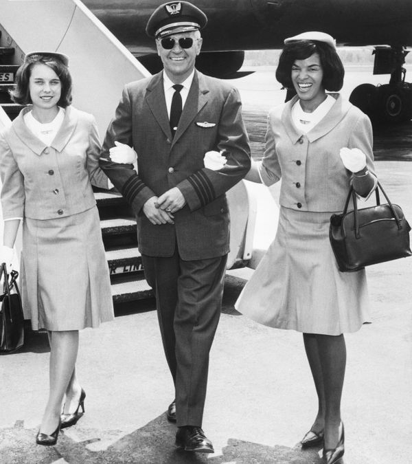 United Airlines' Capt. L.L. Treece escorts stewardesses Carol DiPasalegne and JoAnn Tartaul to the crew lounge after&nb
