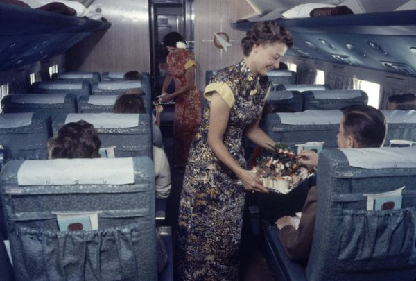Flight attendants serve food and drinks to passengers on a Japan Airlines plane in 1958.