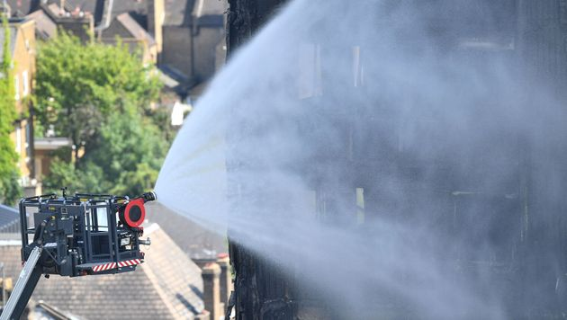 Firefighters spray water after a fire engulfed the 24-storey Grenfell Tower in west