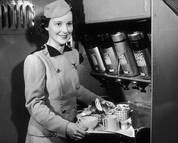 A Canadian Colonial Airways flight attendant with a tray of food and refreshments in the 1940s.
