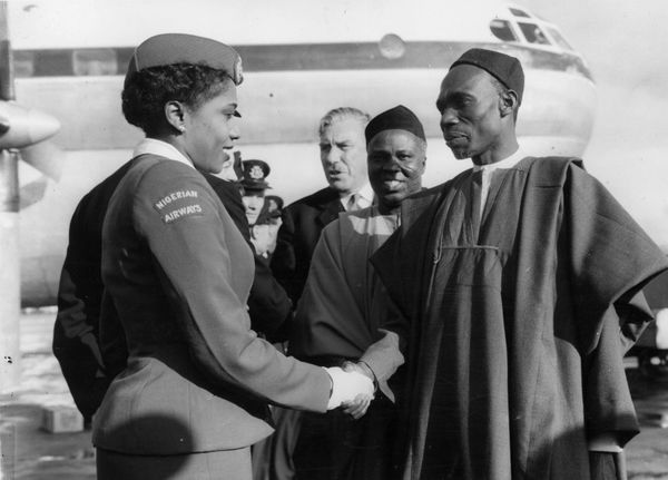 Nigerian Prime Minister Abubakar Tafawa Balewa greets stewardess Christina Twsela after the inaugural flight of Nigerian Airw