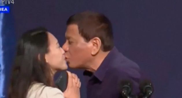 Philippine President Rodrigo Duterte plants a kiss on a Filipino woman's