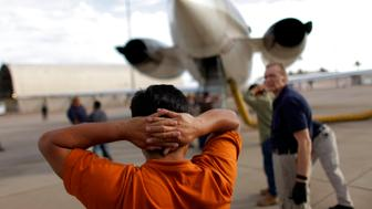 A Guatemalan illegal immigrant prepares to board a plane at a flight operations unit at the Phoenix-Mesa Gateway airport during his deportation process in Mesa, Arizona July 10, 2009. As President Barack Obama tries to rally support in the U.S. Congress to revive comprehensive immigration reform this year, his government is removing the United States' unauthorized population at a gathering pace. ICE's Flight Operations Unit, carrying out a policy begun under former President George W. Bush, has moved an average of 4,200 unauthorized migrants a week this year, up from 3,700 last year. Picture taken July 10, 2009. To match feature USA/DEPORTATIONS.  REUTERS/Carlos Barria  (UNITES STATES POLITICS)