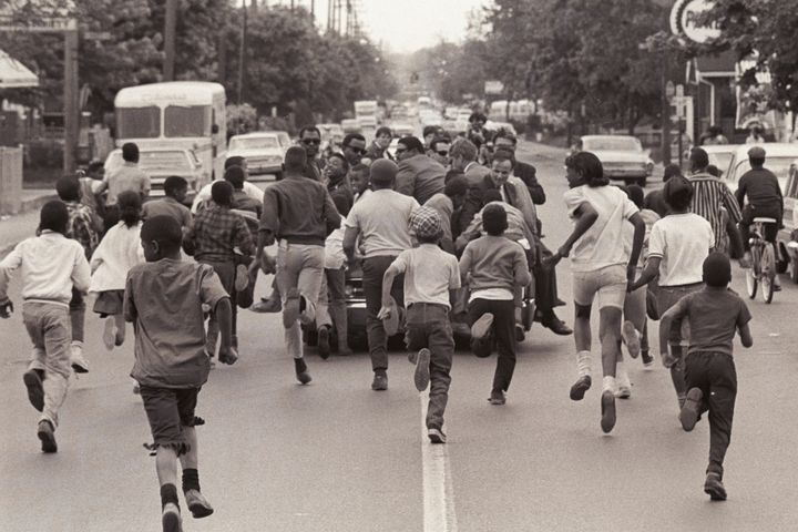 A group of children run after an open-top convertible carrying Kennedy, then a senator from New York, as he campaigned f