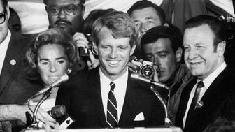 Sen. Robert Kennedy (C) addressing crowd from stage w. wife Ethel, former football star Rosey Grier & photographer Bill Eppridge standing in bkgrd., & LA mayor Jesse Unruh (2R), moments before Kennedy's assassination, Ambassador Hotel.  (Photo by Julian Wasser/The LIFE Images Collection/Getty Images)