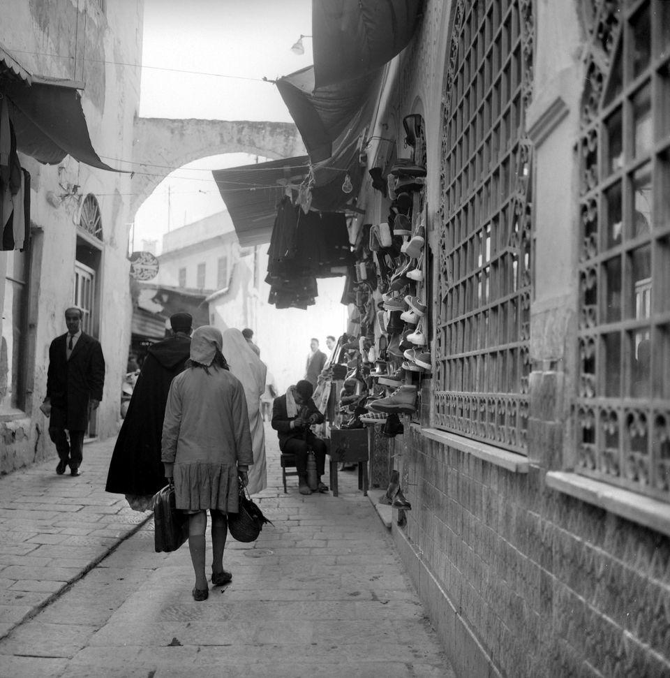 Une jeune fille traverse la rue de la Kasbah en passant par un