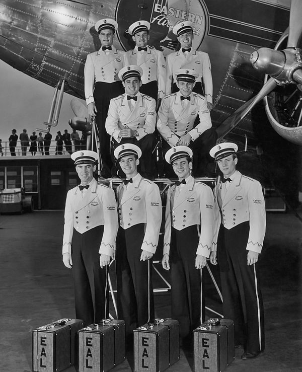 Eastern Airlines flight stewards pose in their uniforms in front of their aircraft, circa 1945.