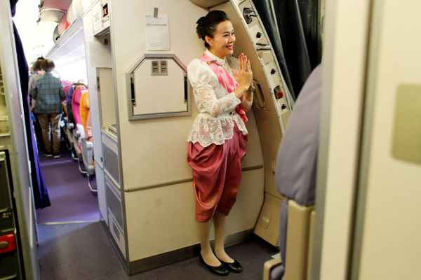 A Thai Airways flight attendant welcomes passengers in 2018.