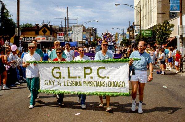 Near the intersection of North Broadway and West Barry Avenue, participants march behind a banner that reads 'G.L.P.C., Gay &