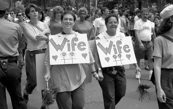 Two women wearing 'Wife' signs around their necks, smile for the camera, at the 1989 gay Pride parade in Greenwich Village, M