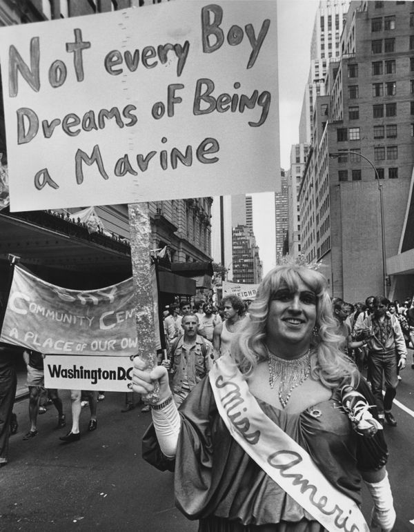 A gay rights protester in drag with a banner declaring 'Not Every Boy Dreans Of Being A Marine' during a gay rights march up