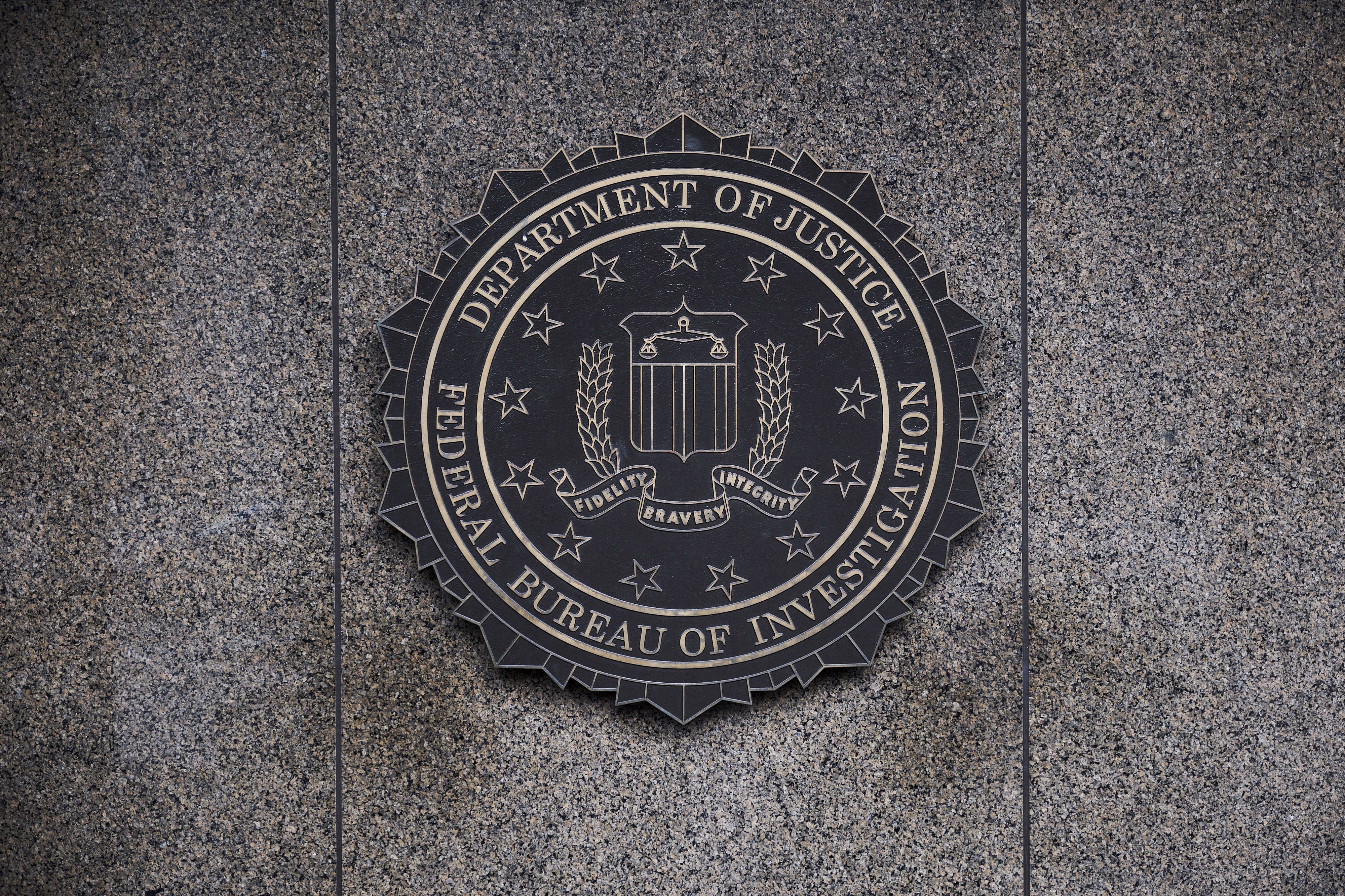 The Federal Bureau of Investigation seal is displayed outside FBI headquarters in Washington, D.C., U.S., on Friday, Feb. 2, 2018. FBI and Justice Department officials got a warrant to spy on a Trump campaign associate by misleading a surveillance court judge, House Republicans contend in a newly released memo that Democrats have dismissed as a contrived account intended to protect the president. Photographer: T.J. Kirkpatrick/Bloomberg via Getty Images