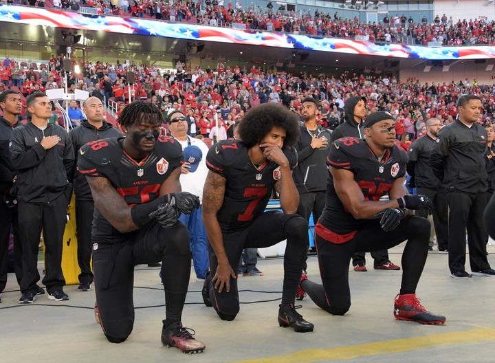Former San Francisco 49ers quarterback Colin Kaepernick (middle) and his teammate Eric Reid (No. 35) began kneeling in 2016 t