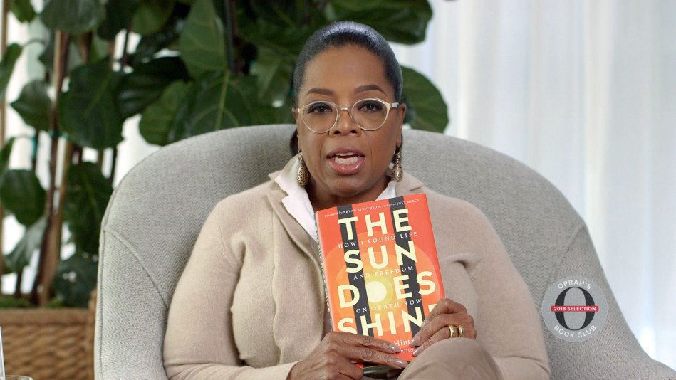 Oprah holding her latest Book Club selection: The Sun Does Shine by Anthony Ray Hinton