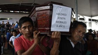 Two men carry the coffin of a little girl who died, following the eruption of the Fuego volcano, along the streets of Alotenango municipality, Sacatepequez, about 65 km southwest of Guatemala City, on June 4, 2018. - Rescue workers Monday pulled more bodies from under the dust and rubble left by an explosive eruption of Guatemala's Fuego volcano, bringing the death toll to at least 62. (Photo by JOHAN ORDONEZ / AFP)        (Photo credit should read JOHAN ORDONEZ/AFP/Getty Images)