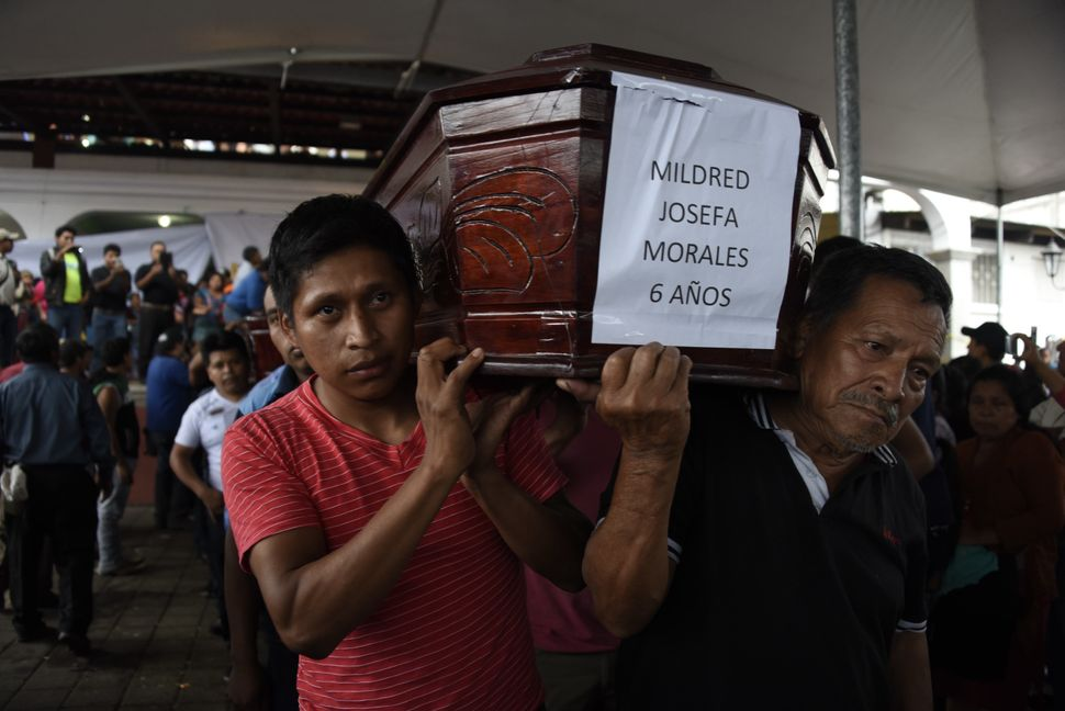 Two men carry the coffin of a little girl who diedfollowing the eruption of the Fuego volcano.