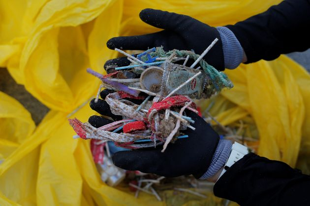 A volunteer shows plastics from a garbage collection on the Atlantic coast in Rota Spain, June