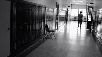 Black and white photograph at an angle of a school hallway which has a bright window at the end. There are lockers and classroom doors and there is a silouette of a person walking at the end of the hall. Has an erie feel- like a dream.