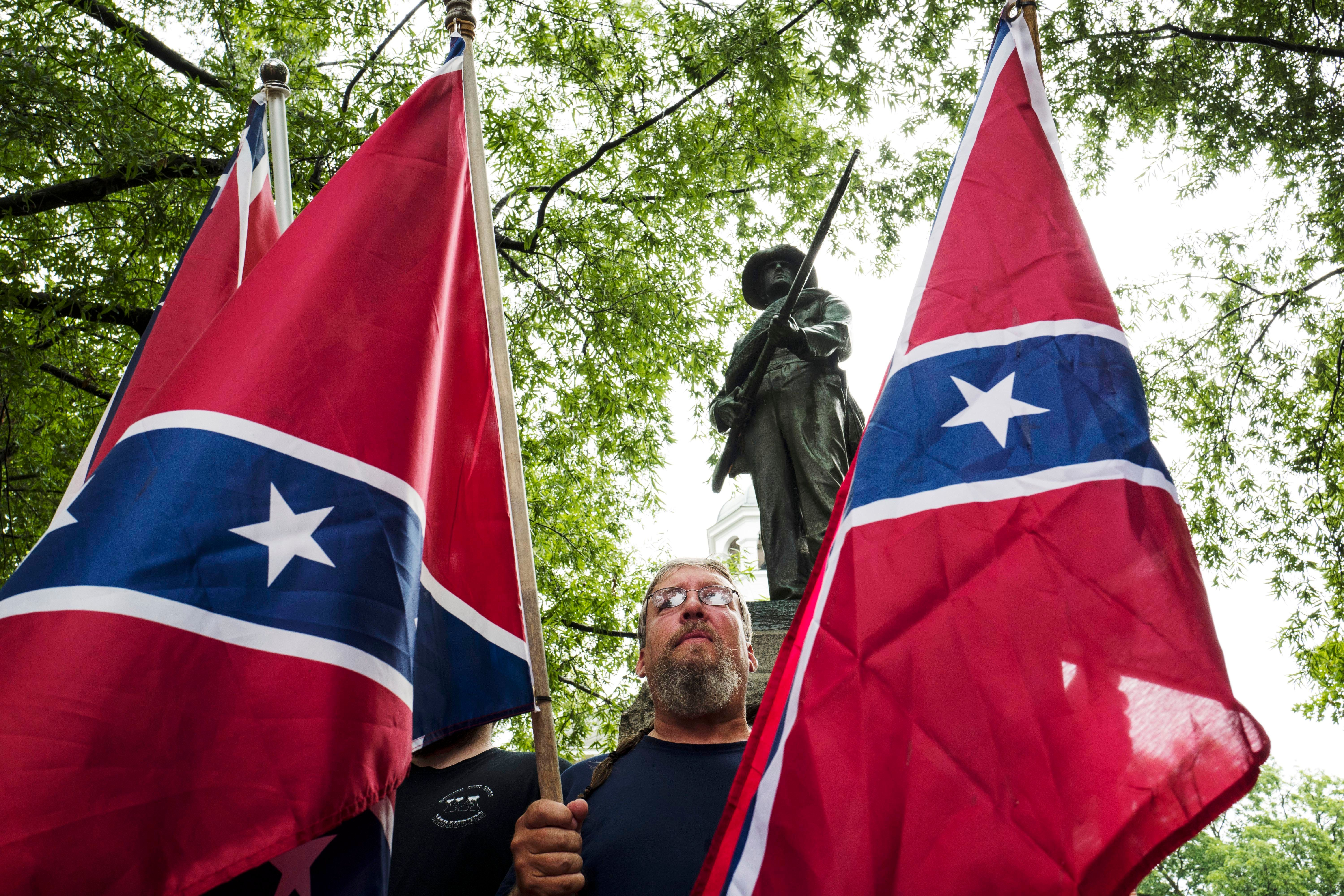 LEESBURG, VA    JULY 18:  Tom McGuigan, of Fauquier County, hoists Confederate flags in support of the Confederate Soldier Monument on the grounds of the Loudoun County Courthouse in Leesburg, Virginia, on Saturday, July 18, 2015.  Nearby, the Loudoun County Branch of the NAACP held a rally in remembrance of the slaves sold on the steps of the courthouse and the Union soldiers who died liberating Loudoun County. (Photo by Nikki Kahn/The Washington Post via Getty Images)