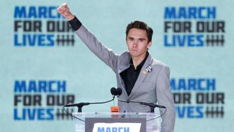 "David Hogg, a student at the Marjory Stoneman Douglas High School, site of a February mass shooting which left 17 people dead in Parkland, Florida, thrusts his fist in the air as he speaks during the ""March for Our Lives"" event demanding gun control after recent school shootings at a rally in Washington, U.S., March 24, 2018. REUTERS/Aaron P. Bernstein"