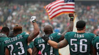 PHILADELPHIA, PA - OCTOBER 08: Rodney McLeod #23, Malcolm Jenkins #27 of the Philadelphia Eagles raise their fists in protest during the playing of the National Anthem as teammate Chris Long #56 shows support before a game against the Arizona Cardinals at Lincoln Financial Field on October 8, 2017 in Philadelphia, Pennsylvania. The Philadelphia Eagles defeated the Arizona Cardinals 34-7. (Photo by Rich Schultz/Getty Images)