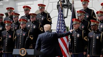 """U.S. President Donald Trump touches a member of the United States Army Chorus as he departs a """"celebration of America"""" event on the South Lawn of the White House in Washington, U.S., June 5, 2018. The event was arranged after Trump canceled the planned visit of the Super Bowl champion Philadelphia Eagles to the White House. REUTERS/Carlos Barria"""