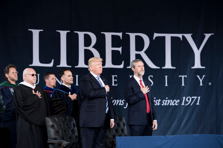 President Donald Trump and the president of Liberty University, Jerry Falwell, right, recite the Pledge of Allegiance during