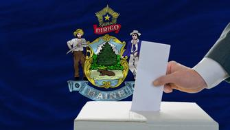 man putting ballot in a box during elections  in front of flag american state of maine