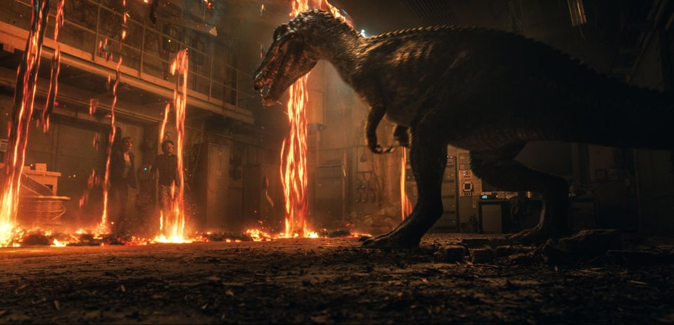 Bryce Dallas Howard and Justice Smith cower before a baryonyx in