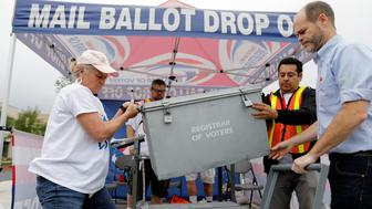 Election workers take away a ballot box full of votes at a drive-through mail-in ballot return drop set-up outside the Registrar of Voters office in San Diego, California, U.S., June 5, 2018. REUTERS/Mike Blake