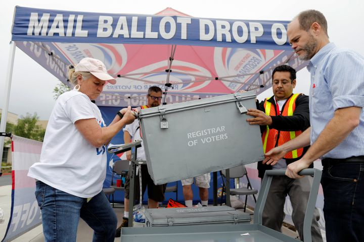 Election workers take away a ballot box full of votes at a drive-through ballot drop-off site in San Diego on Tuesday.