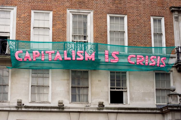 Protestors hang anti-capitalism slogans on buildings on Clarges Street in London during the demonstrations...