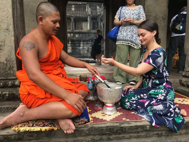 Getting a blessing from a Buddhist monk in Angkor Wat,
