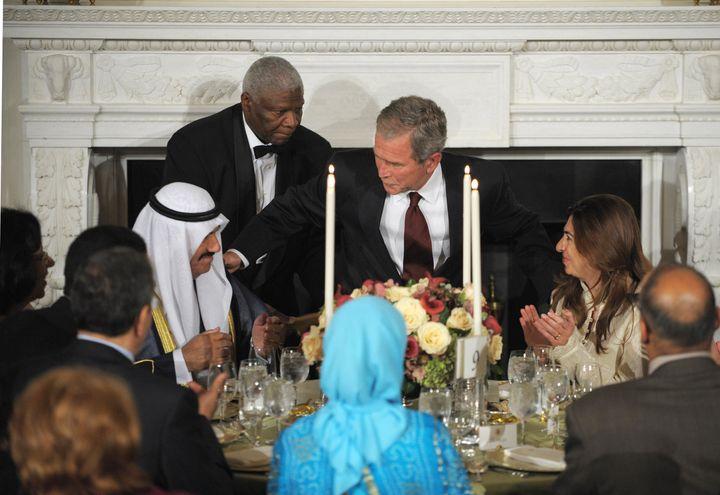 President George W. Bush takes his seat next to Kuwait's former Prime Minister Nasser al-Mohammed al-Ahmed al-Jaber al-Sabah