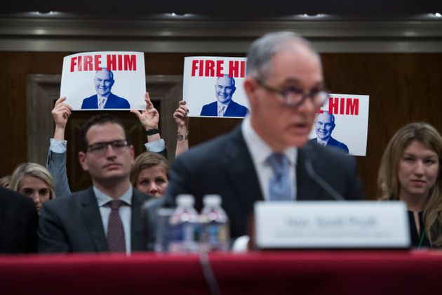 Protesters hold signs as Pruitt testifies during a Senate hearing on the proposed fiscal year 2019 budget...