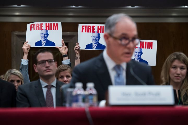 Protesters hold signs as Pruitt testifies during a Senate hearing on the proposed fiscal year 2019 budget for the EPA in