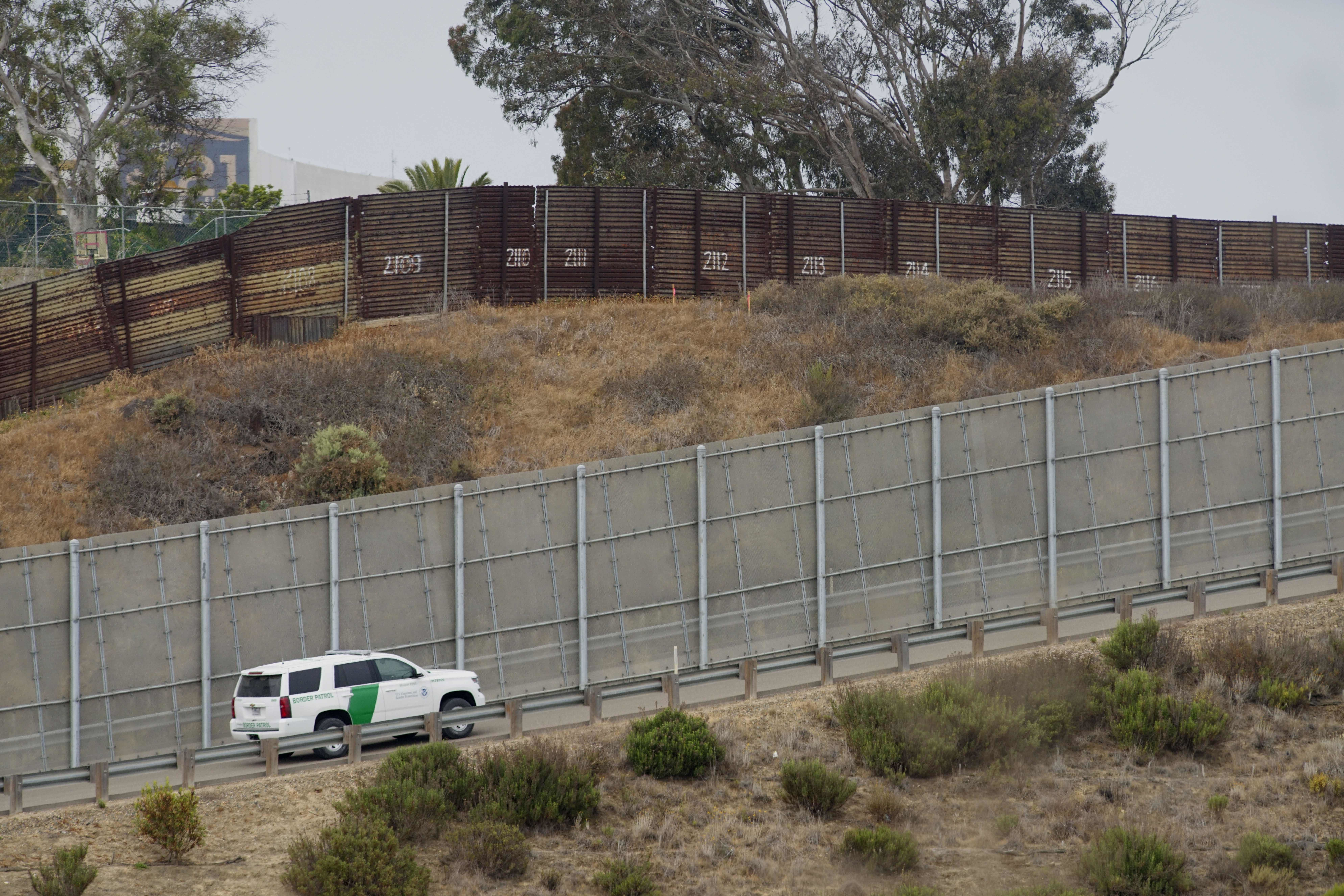 A Border Patrol car drives past the old border wall just east of where construction is set to begin on new fencing in San Ysi
