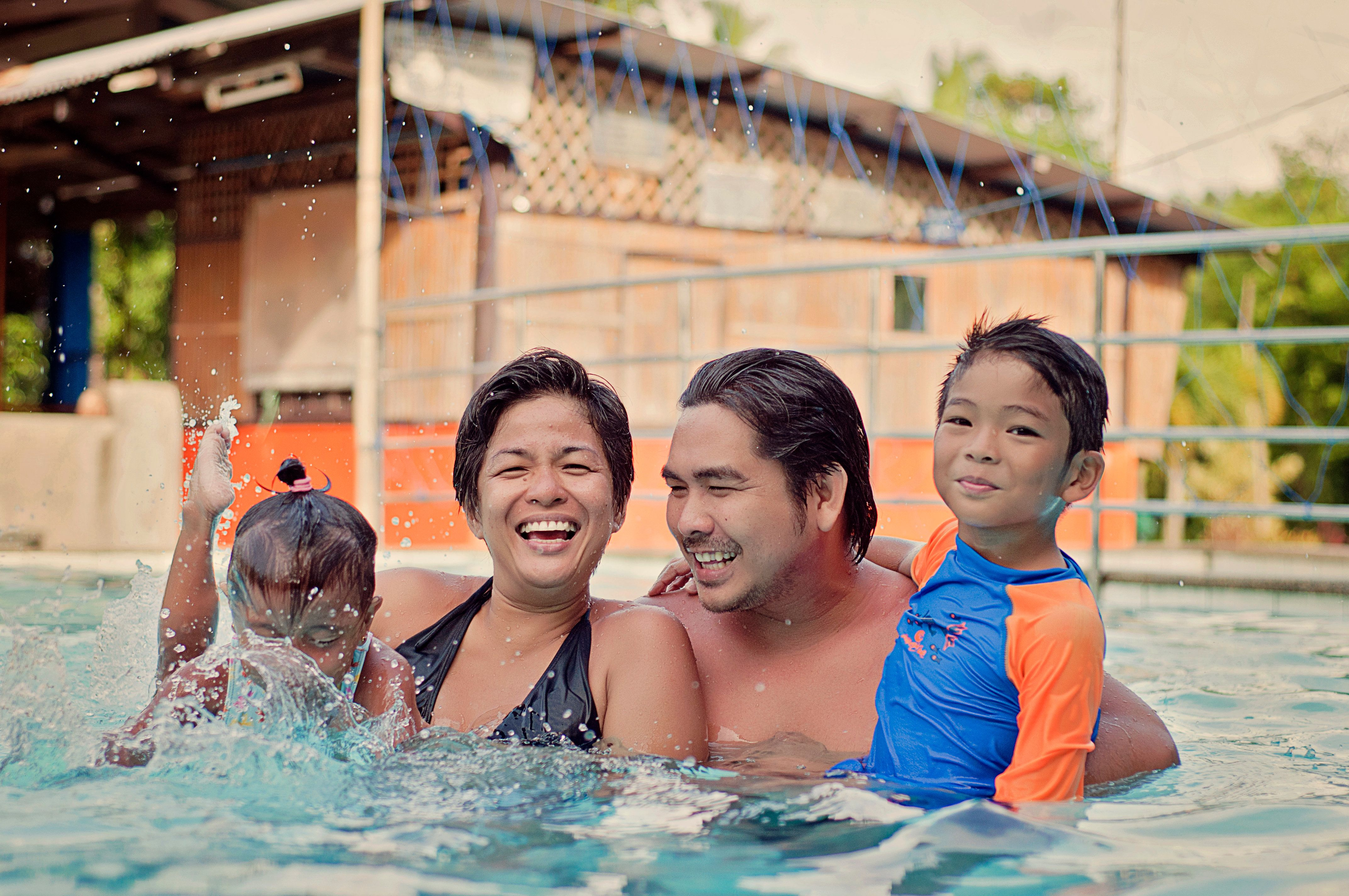 Asian family of four in swimming pool.