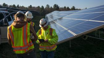 OXFORD, MASSACHUSETTS - DECEMBER 4: Employees from a Radian Generation's operations and maintenance team exchange technical notes after they have changed out a faulty solar inverter along a row of solar panels December 4, 2017 at the Clara Barton Road facility in Oxford, Massachusetts. The 1.4 megawatt solar array is owned and operated by BlueWave Solar which feeds the generated electricity to homes and small businesses and to the Phillips Academy Andover private school. (Photo by Robert Nickelsberg/Getty Images)