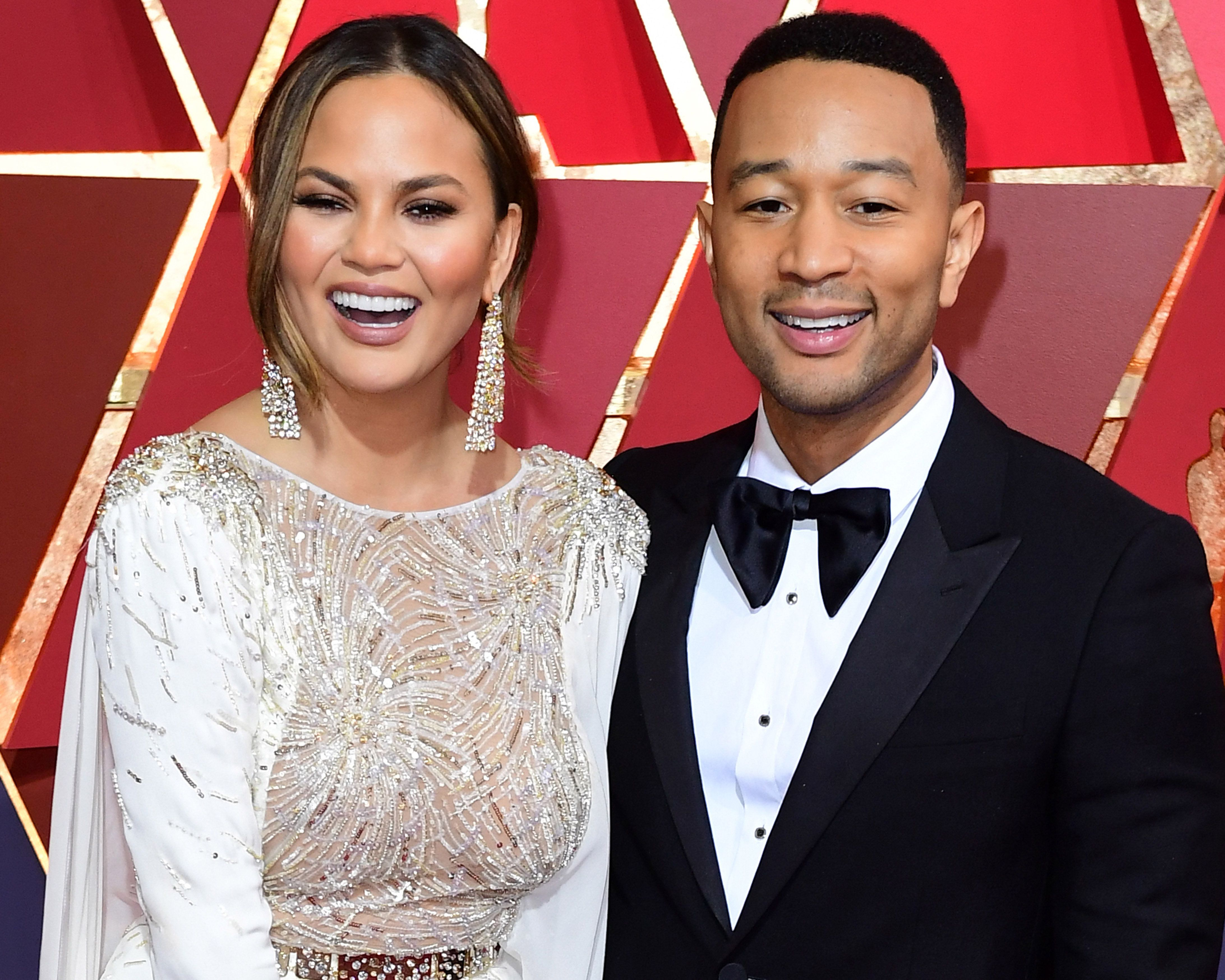File photo dated 26/02/17 of Chrissy Teigen and John Legend, as Chrissy has scolded her husband for taking all of her phone chargers.